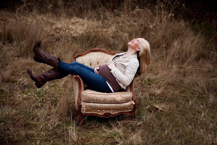 Sesión de maternidad chica sentada en un sillón tocando su barriga