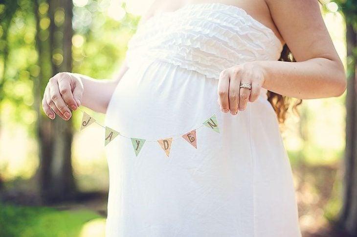 Sesión de fotos de maternidad chica sosteniendo el nombre de su bebé junto a su vientre