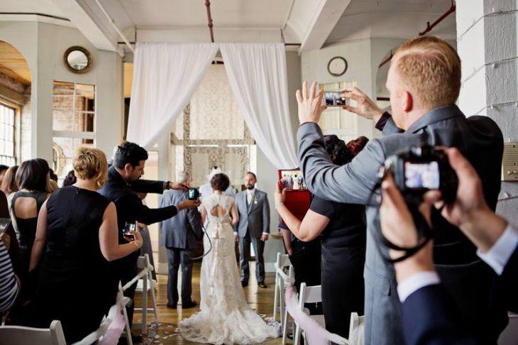 Personas tomando fotografías de una boda, interrumpiendo la ceremonia