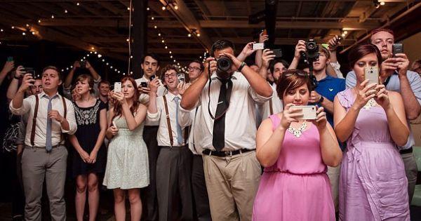 Invitados tomando fotos en una boda