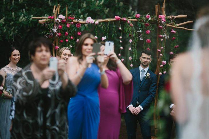 Personas tomando múltiples fotos de una boda siendo los invitados
