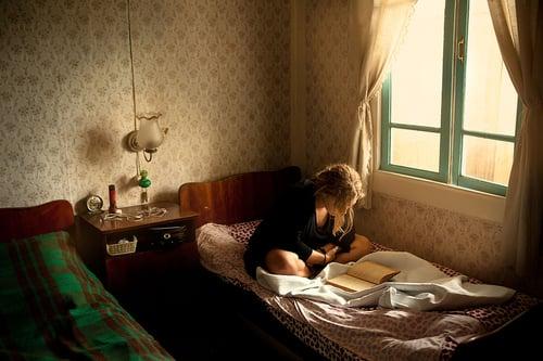 Chica sentada en una cama leyendo un libro