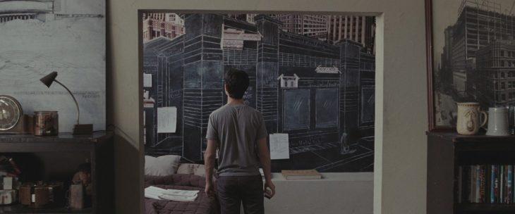 Escena de la película 500 días con ella, tom dibujando en la pared de su departamento