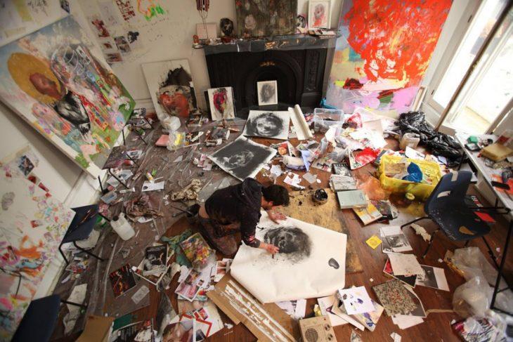 chico que es pintor tirado en el suelo dibujando un cuadro