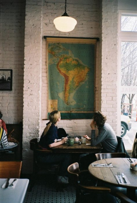 pareja de novios viendo un mapa en una pared mientras toman café