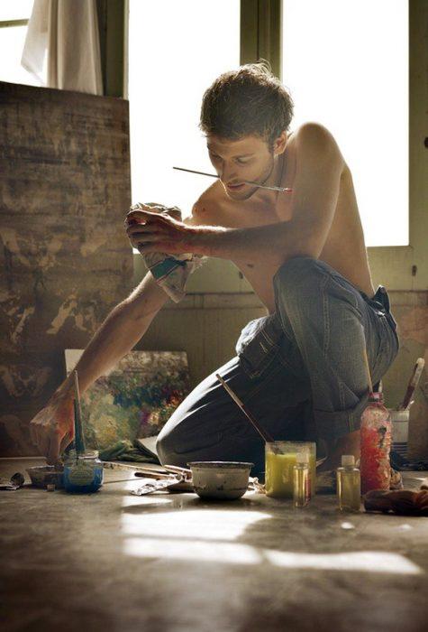 Chico sentado en su estudio pintando mientras sostiene el pincel con su boca