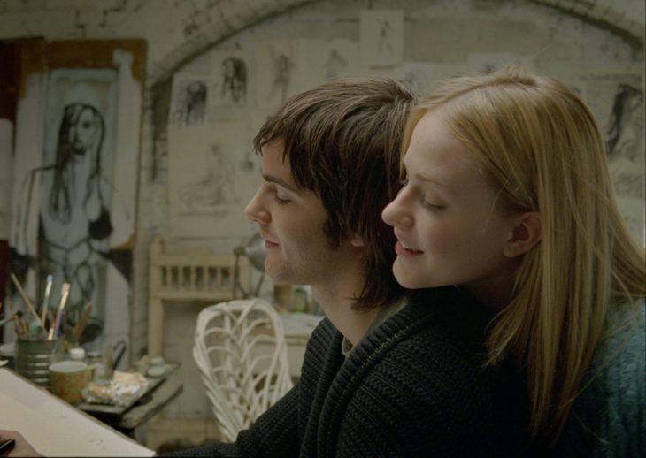 Escena de la película Across the universe chico dibujando mientras una chica lo observa