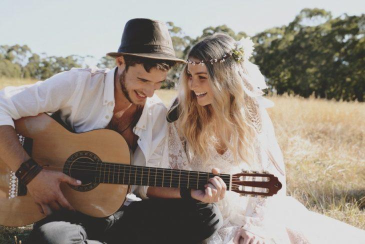Chico sentado junto a una chica tocando la guitarra y riendo