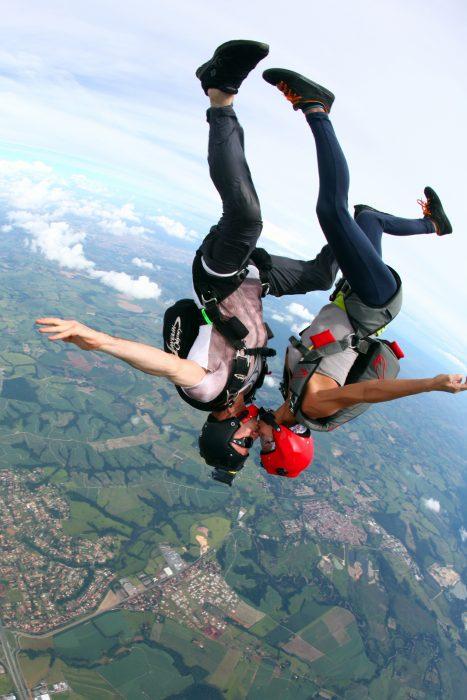 Pareja aventándose de un paracaídas y besandose