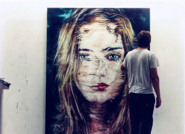 Chico artista dibujando a una mujer en la pared