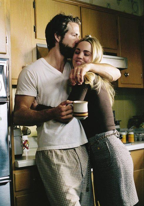 Pareja de novios abrazados en la cocina de su casa