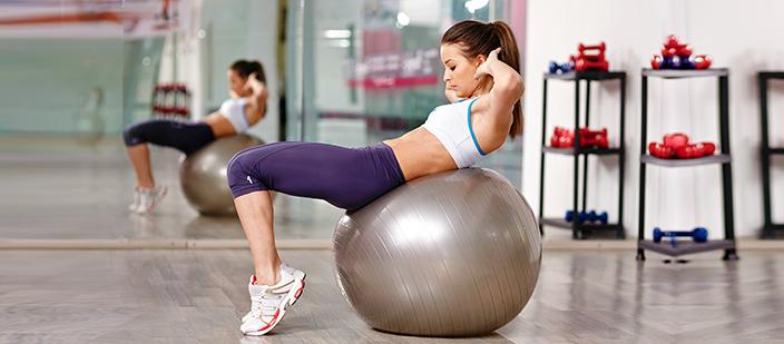 Chica practicando ejercicios con una pelota de yoga