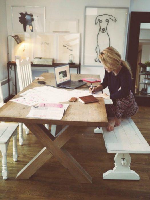Chica trabajando sobre la mesa de su cocina