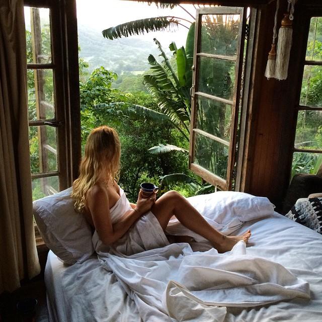 Chica sentada en la cama frente a una ventana tomando café