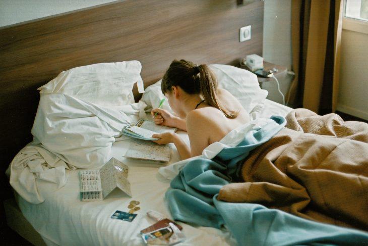 Chica escribiendo en una libreta mientras está recostada boca abajo en su cama