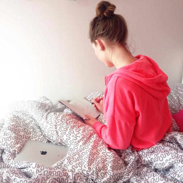Chica anotando cosas en una agenda mientras esta sentada en su cama