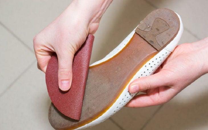 mujer frotando suela de zapato con lija