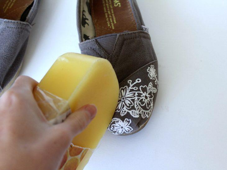 persona frotando zapatos de tela con cera de abeja