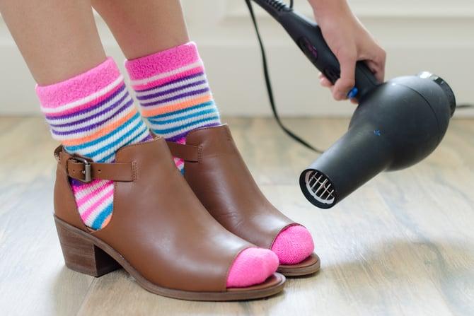 mujer calentando zapatos con secadora de cabello