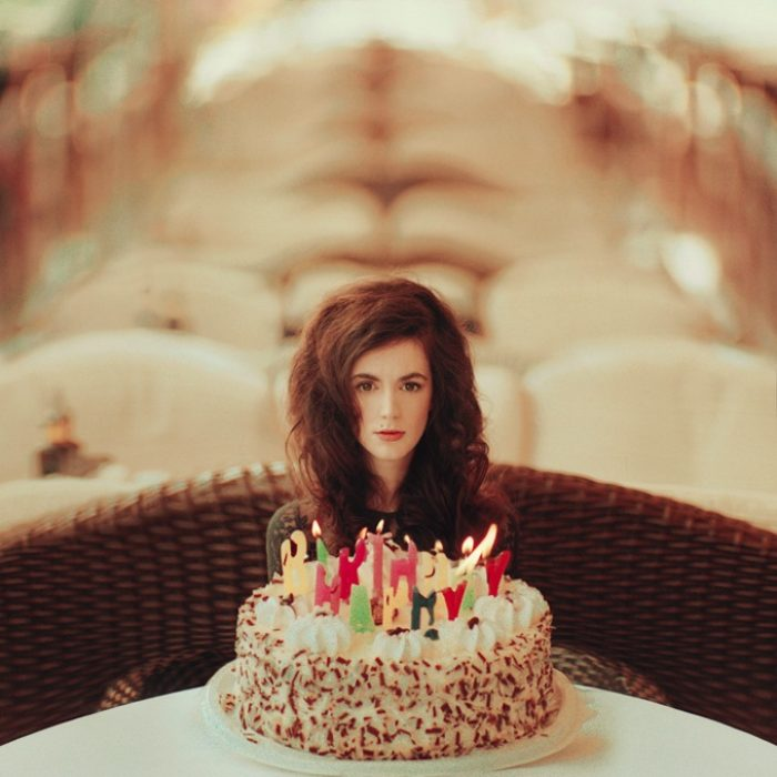 Chica sentada frente a un pastel sola