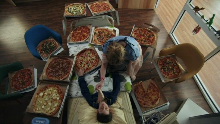Chico recostado en la cama comiendo pizza
