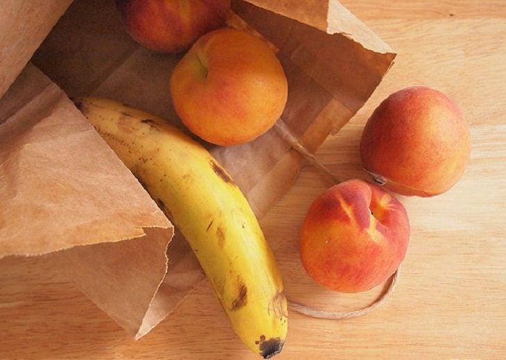 plátanos y duraznos en bolsa de papel