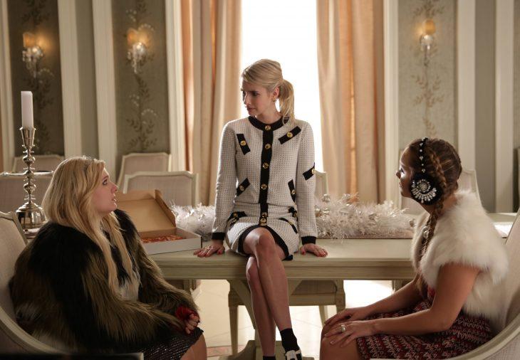 Escena de la serie scream queens channel sentada en una mesa hablando con sus amigas