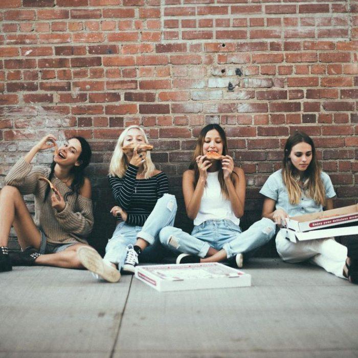 Chicas sentadas en la banqueta y recargadas den la pared comiendo pizza