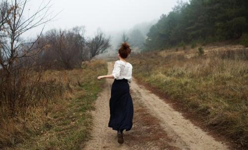 Chica corriendo por un campo