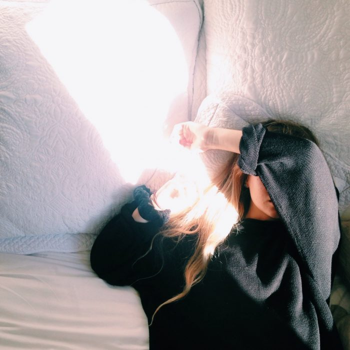 Chica recostada en una cama tapando su cara con un brazo