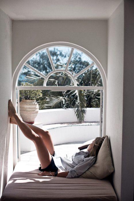 Chica recostada en un sofá frente a la ventana