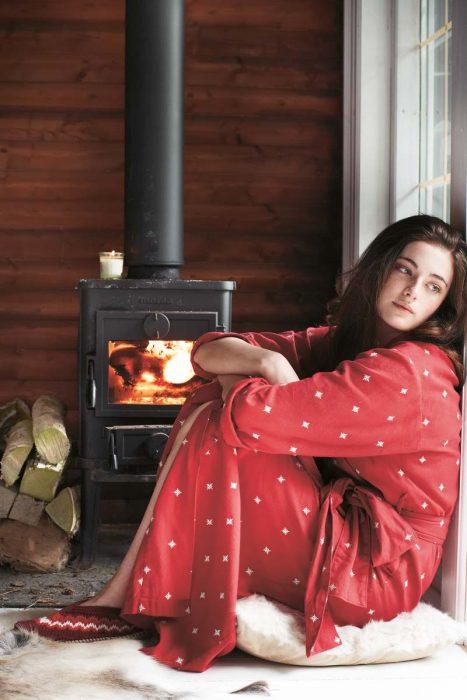 Chica sentada frente a una chimenea viendo hacia la ventana y pensando