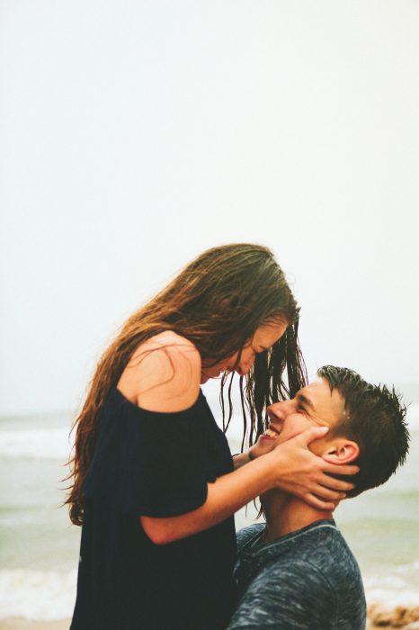 Pareja de novios en una playa mirándose a los ojos