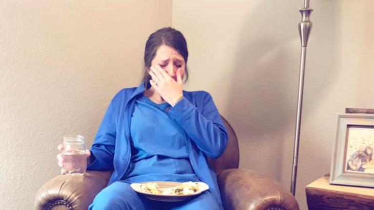 Enfermera llorando en el sofá de su casa
