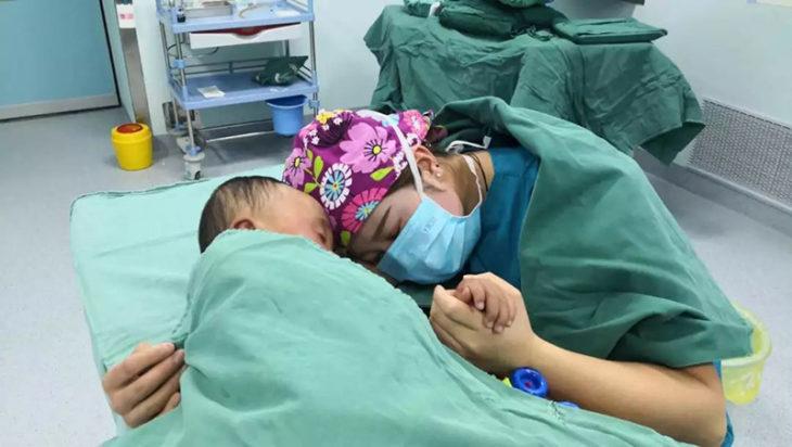Enfermera junto a un niño tomados de la mano dentro de un quirofano