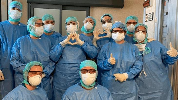 Grupo de enfermeros haciendo señas con sus maos en forma de corazón y bienestar para mostrar su amor por su trabajo
