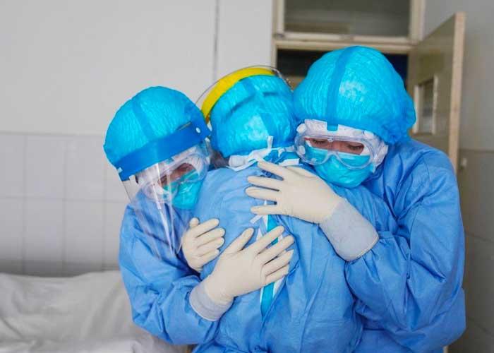 Grupo de enfermeras con trajes de protecciòn contra Covid-19, abrazadas dentro de una sala de hospital