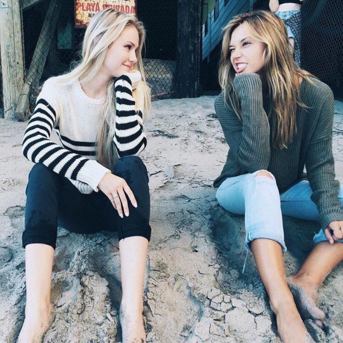 Chicas sentadas en la playa haciendo caras