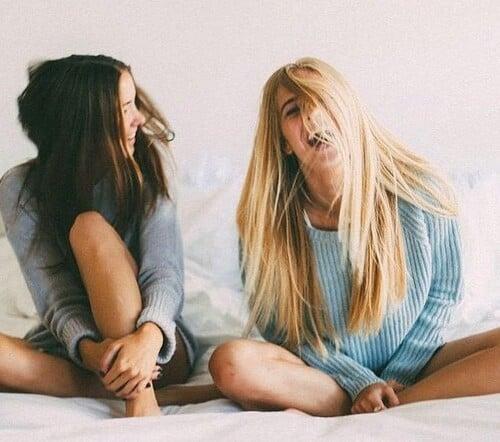 Chicas sentadas en una cama riendo