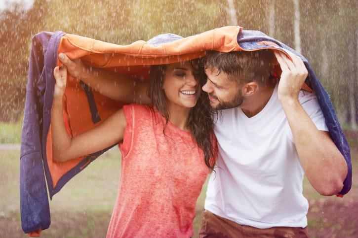 hombre cubriendo a mujer de la lluvia