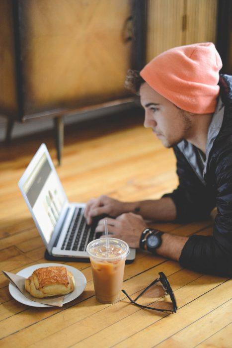 Chico desayunando mientras está frente a una computadora
