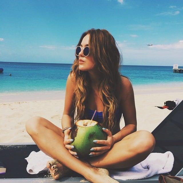Chica tomando agua de coco en la playa