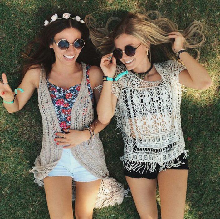 Chicas tiradas en el pasto riendo felices