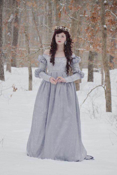 Chica usando un vestido de color lila mientras está parada en la nieve