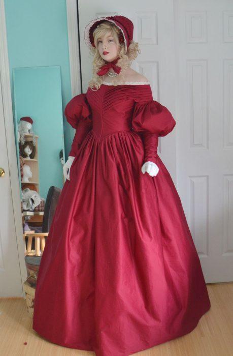 Chica usando un vestido rojo medieval con un sombrero a juego