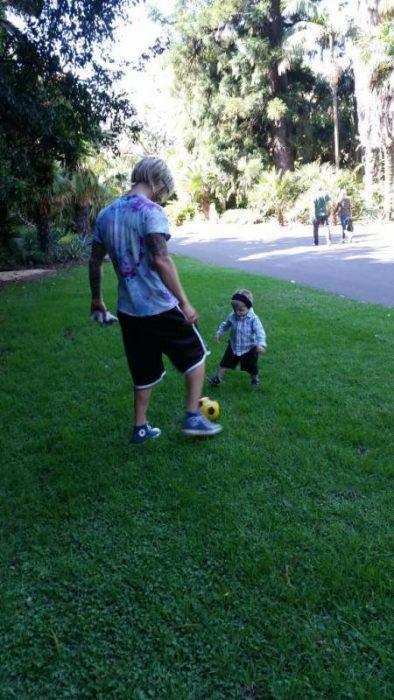 Hombre jugando con un niño a la pelota, ambos con la enfermedad de Treacher Collins