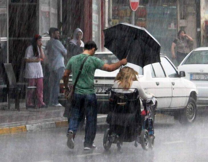chico cubriendo con paraguas a mujer en silla de ruedas