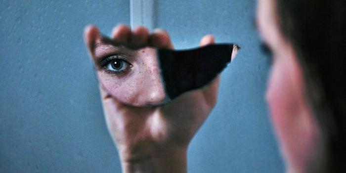 mujer viendose en pedazo de espejo