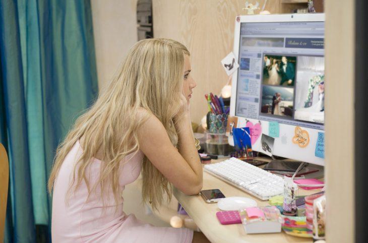 Chica viendo fotos de boda en una computadora
