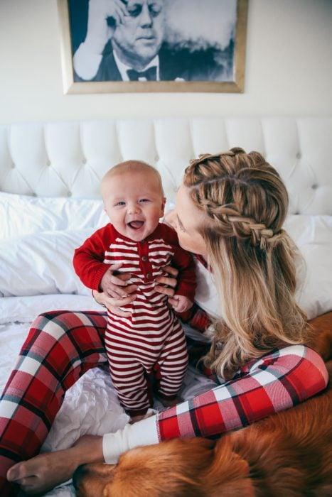Chica sosteniendo un bebé en la cama